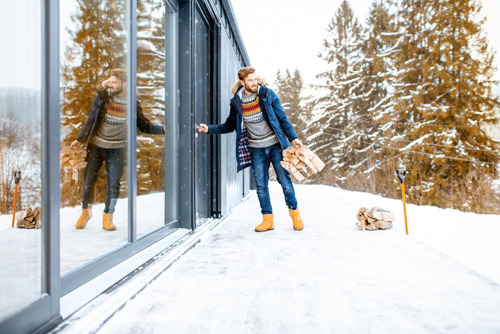 Homme qui entre dans sa maison depuis sa terrasse couverte de neige.