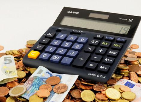 Caculatrice et pièces de monnaie. Economies d'impôts