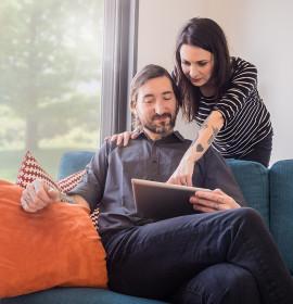 Couple qui consulte une tablette dans son salon